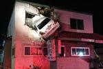 Xe ô tô bay, treo lơ lửng trên tầng 2 tòa nhà ven đường
