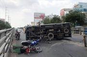 Xe tải mất lái đâm đổ dải phân cách rồi lật ngang trên cầu vượt Cây Gõ