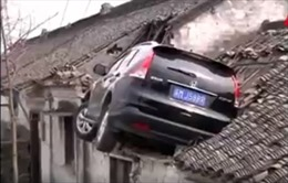 Ô tô mất lái bay tót lên mái nhà dân, tài xế phải leo thang đi xuống