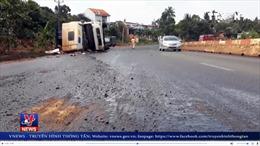 Xe container lật ngang, hàng trăm lít dầu điều đổ tràn ra đường