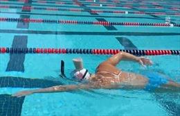 Xem vận động viên Olympic giữ thăng bằng cốc sữa trên đầu khi bơi