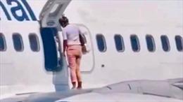 Nữ hành khách mở cửa thoát hiểm đi dạo trên cánh máy bay