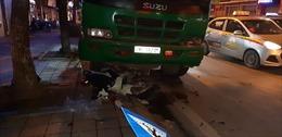 Xe chở rác cán nát xe máy đang dừng chờ đèn đỏ, đâm đổ cột đèn