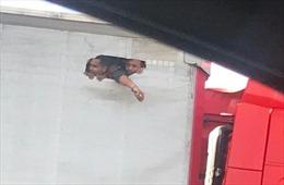 Người nhập cư bị nhốt tuyệt vọng đục lỗ trên thùng xe tải nhìn ra ngoài