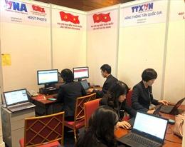 Các phóng viên tác nghiệptại Trung tâm báo chí trong ngày đầu làm việc của Đại hội Đảng XIII