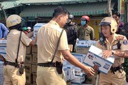 CSGT và người dân giúp tài xế gom sữa từ xe tải bị lật nghiêng