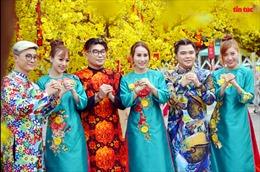 Người dân TP Hồ Chí Minh diện áo dài dạo phố ông đồ, e ấp bên mai vàng