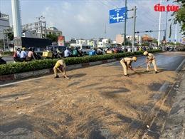 Cảnh sát giao thông đội nắng rải cát lên mặt đường trơn trượt do dầu ăn